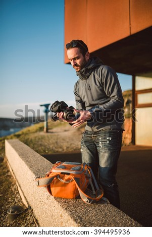 Adult photographer preparing his equipment to a shooting outdoors - stock photo