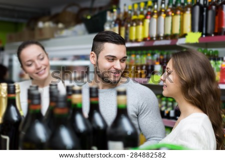 Adult positive shoppers choosing bottle of wine at liquor store - stock photo