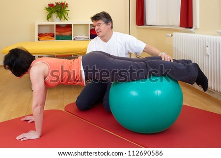 adult practicing poses on exercise ball with professional - stock photo