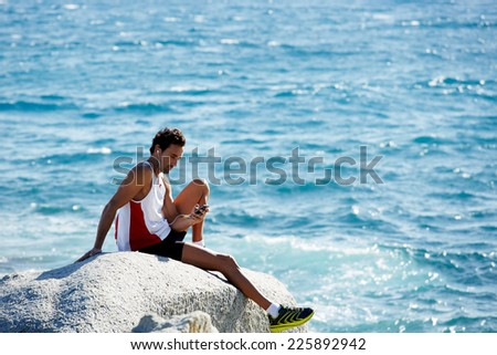 Adult runner resting after intensive fitness training on the beach, muscular build fit man taking a break listening to music on his mobile phone while sitting on big rock at the sea - stock photo