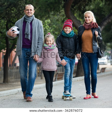 adult russian spouses with children posing in autumn park and smiling 