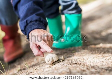Adult's and kid's legs in rubber boots near the snail. Image with selective focus - stock photo