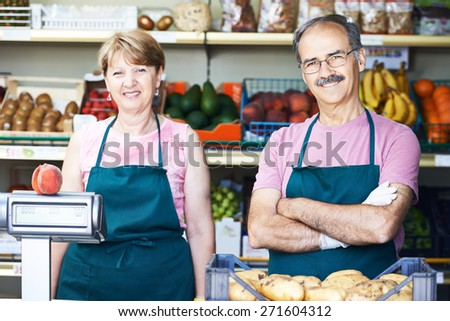adult senior sale man with female assistant in fruit vegetable market shopping store - stock photo
