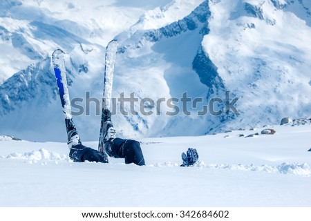Adult skier lying in deep snow at the ski resort - stock photo