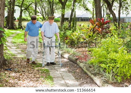 Adult son helping his father use a walker in the park. - stock photo
