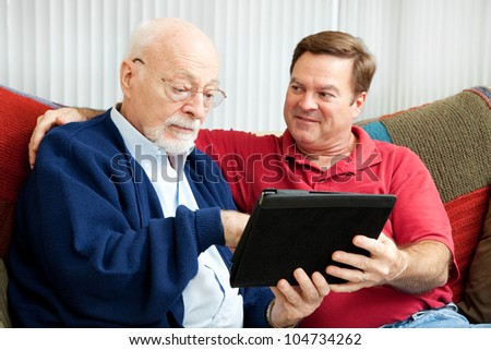 Adult son teaching his father to use a new tablet PC .