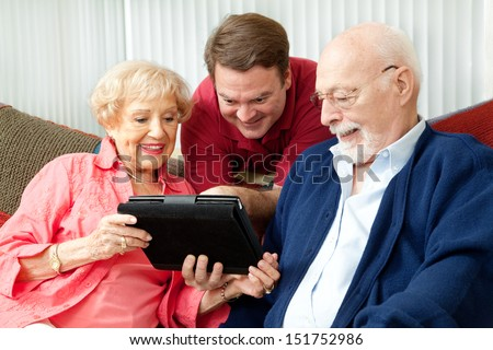 Adult son teaching his parents to use their new tablet pc computer.   - stock photo