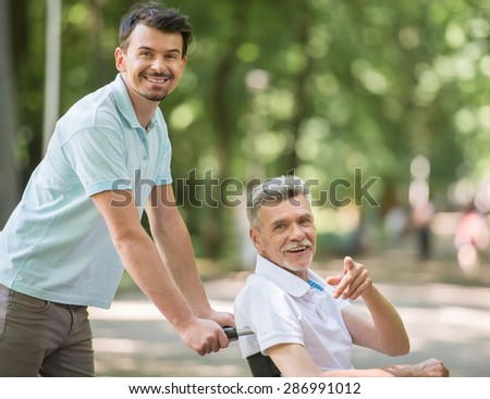 Adult son walking with disabled father in wheelchair at park. - stock photo