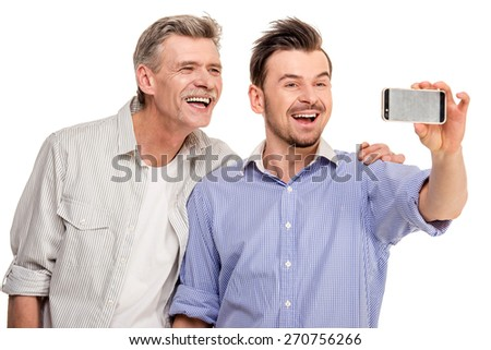 Adult son with senior father doing selfie, isolated white background. - stock photo