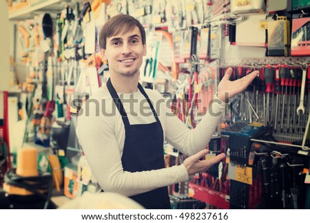 adult spanish male seller posing at tooling section of household store