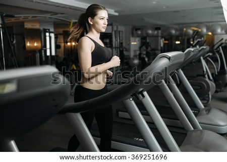 Adult sport woman running on treadmill in gym - stock photo