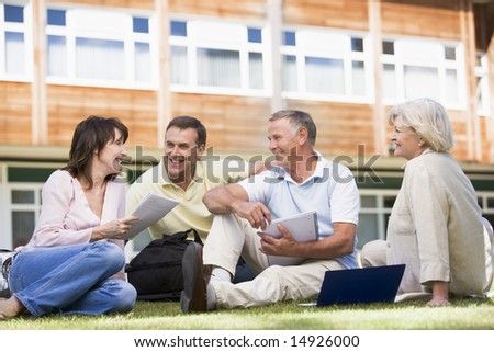 Adult students sitting on a campus lawn - stock photo
