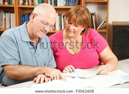 Adult students studying together in the library. - stock photo