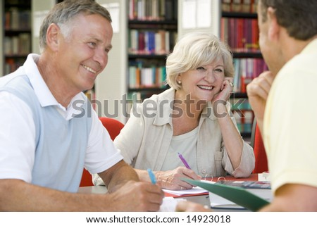 Adult students working together in a library - stock photo