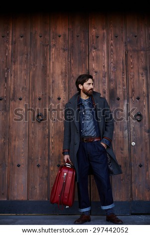 Adult successful business man with a beard in an expensive autumn clothes holding a large suitcase,male tourist standing near large old wooden door with copy space for your text message or advertising - stock photo