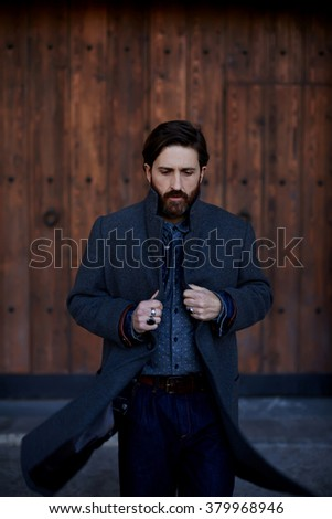 Adult successful businessman with beard dressed in stylish clothes walking outdoors during work break, fashion male designer looking down while standing outside near brown wooden wall in fall day - stock photo