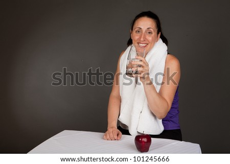 Adult sweating woman with towel after a workout having water and an apple - stock photo