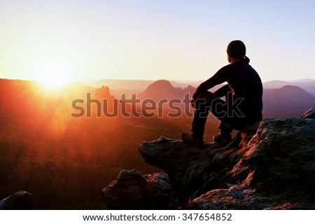 Adult tourist in black trousers, jacket and dark cap sit on cliff's edge and looking to misty hilly valley bellow - stock photo