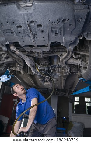 Adult Turkish mechanic draining engine oil at auto repair shop for oil change    - stock photo