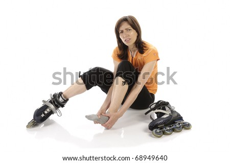 Adult woman (athlete) with in-line skates squats hurt with pain on the ground in front of white background, looking sadly into the camera. - stock photo