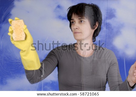 Adult woman cleaning the windows with yellow rubber glove and sponge - stock photo