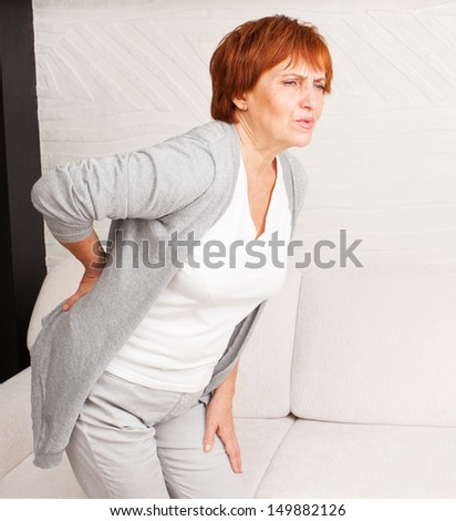Adult woman has a backache. Mature female has pain in back - stock photo