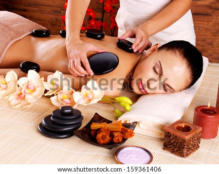 Adult woman having hot stone massage in spa salon. Beauty treatment concept. - stock photo