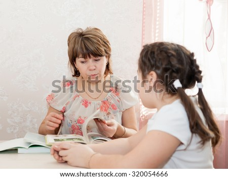 Adult woman helping   to   teenager to learn   lessons at home. - stock photo