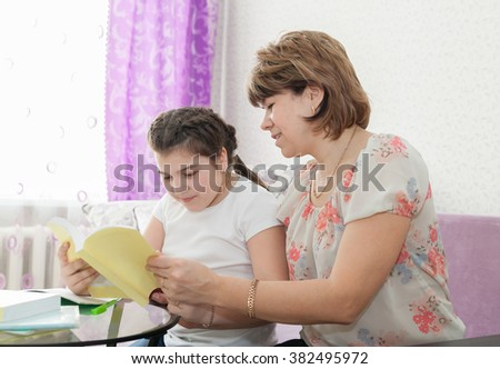 Adult woman helping   to   teenager to learn   lessons at home.