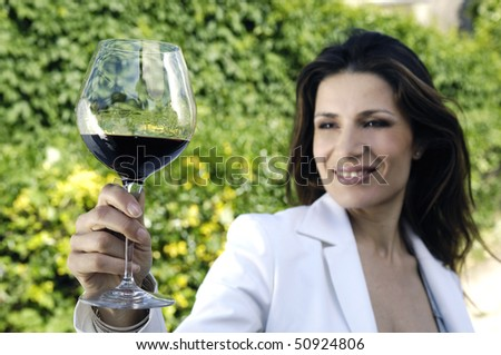 Adult woman holding glass of red wine - stock photo