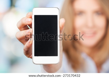 Adult. Woman holding smart phone in hand against green spring background. Blank screen with copyspace - stock photo