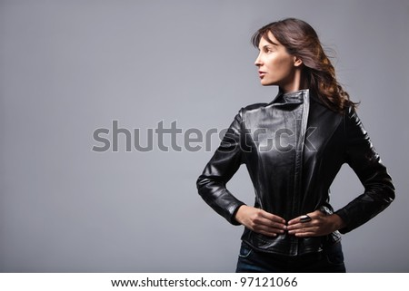 adult woman in black leather jacket, studio shot - stock photo