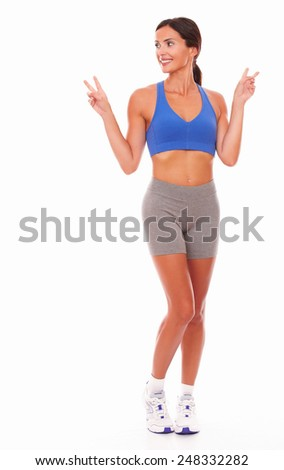 Adult woman in sport clothing looking to her right feeling cheerful and excited on isolated background - copyspace - stock photo