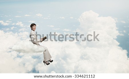 Adult woman in suit with old book in hand sitting on cloud