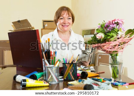 Adult woman painting a flowers in home interior - stock photo
