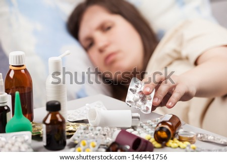 Adult woman patient hand holding vitamin pills lying down bed for cold and flu illness relief - stock photo