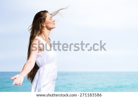 Adult. Woman relaxing at beach enjoying summer freedom with open arms and hair in the wind by the water seaside. Mixed race Asian Caucasian girl on summer travel holidays vacation outside. - stock photo