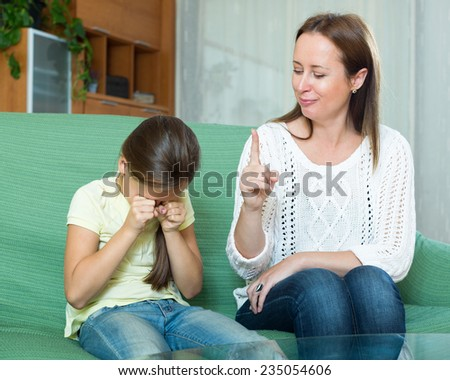adult woman scolding crying little child at home. Focus on woman - stock photo