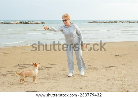 Adult woman walking with a dog on a sea beach. Walking with a pet. Dog - a friend of pensioners. Beach, sea, animals, walk, ocean, fresh air, the resort - the concept of lifestyle old woman retired. - stock photo