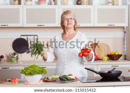 Adult woman working in the kitchen. Mom while she work something else. Mother prepares a salad. Cooking. Woman while preparing food in kitchen. Beautiful adult multiracial woman while making salad. - stock photo