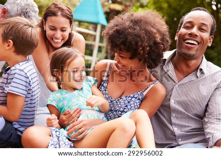 Adults and kids sitting on the grass in a garden - stock photo