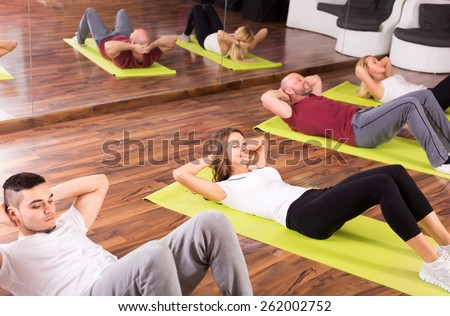 Adults at a fitness school indoor are doing abs - stock photo