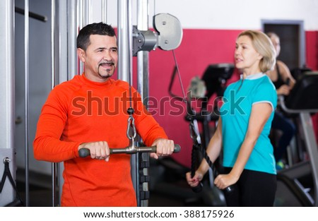 Adults of different age having strength training in gym