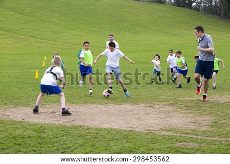 Adults on grassed area with school children supervising a soccer game, Everyone can be seen running and chasing the ball. - stock photo