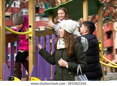 Adults parents helping positive little kids on slide in autumn day - stock photo