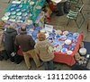 adults who watch the stalls where there are decorated plates for sale at the market - stock photo