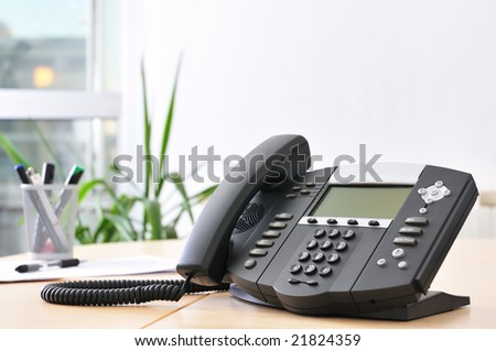 Advanced managerial VoIP phone on beech desk. - stock photo