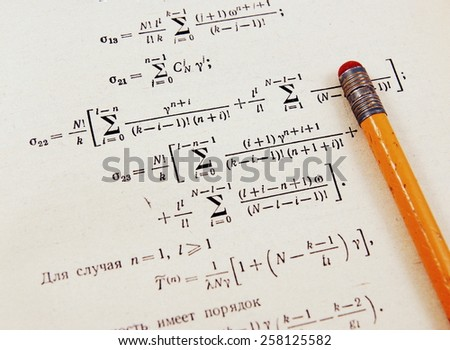 Advanced mathematics (maths): book and pencil in vintage style. Focus on part of the image only - rest is blur by intention  - stock photo
