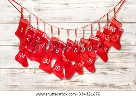 Advent calendar. Christmas decoration red stocking over bright wooden background - stock photo