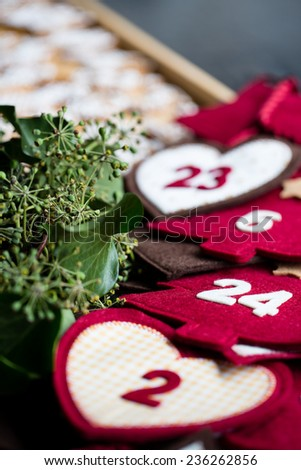 Advent calendar of red and white symbols and numbers with ivy wreath and gingerbread in the background